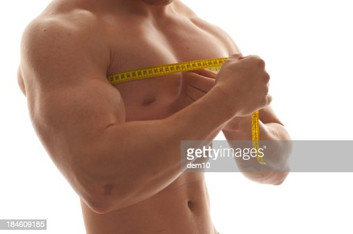 Man measuring his chest with a tape measure : Stock Photo