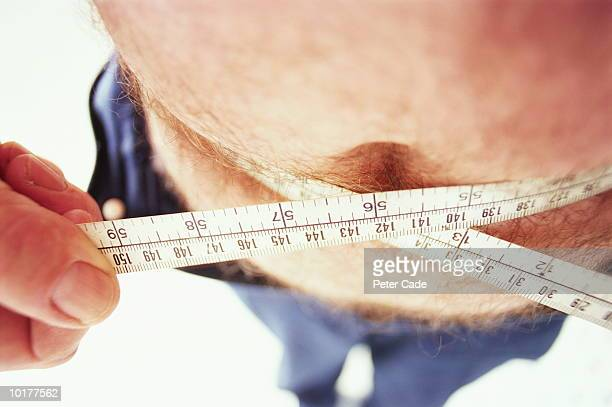 Man measuring waist with tape measure, middle section, elevated view