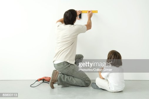 Man measuring wall with a ruler while his son watches, drill on the floor nearby