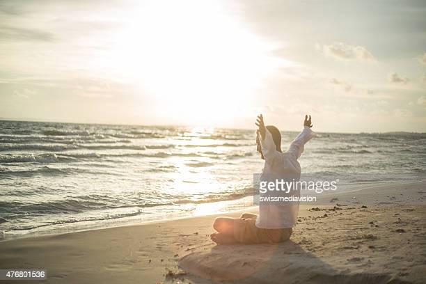 Man meditading on the beach at sunset
