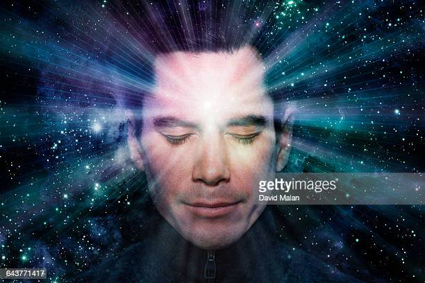 Man meditating with light radiating from him