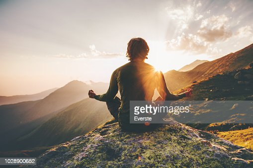 Man meditating yoga at sunset mountains Travel Lifestyle relaxation emotional concept adventure summer vacations outdoor harmony with nature : Stock Photo