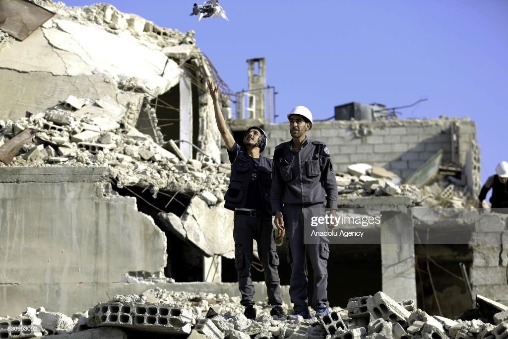 A man, member of Syrian civil defense organization, White Helmets lets a white pigeon to fly for people who lost his life in chemical attack that in the Eastern Ghouta region of Damascus, Syria on August 22, 2017. It is the 4th anniversary of chemical weapons attack near countrysides of Zamalka that Assad Regime's forces carried out.
