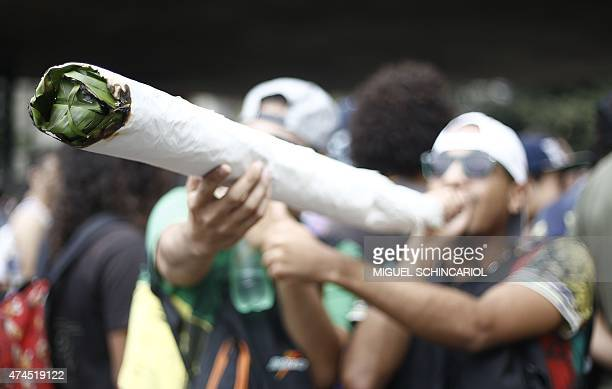 A man mocks to smoke a huge joint during a march calling for the legalization of marijuana at Paulista Avenue in Sao Paulo Brazil on May 23 2015...
