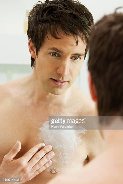Mann feuchtigkeitsspendende Brust im Badezimmer