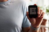 A Man Using Ketone Glucose Blood Meter to monitor his ketogenic diet