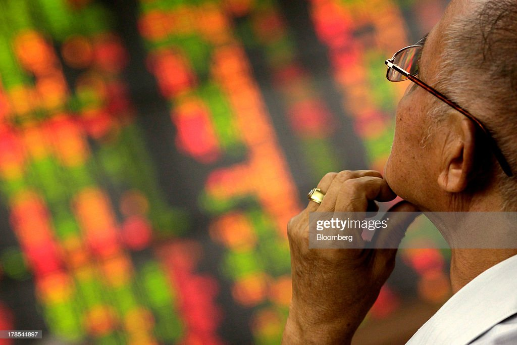 A man monitors an electronic stock board at the Asia Plus Securities Pcl headquarters in Bangkok, Thailand, on Friday, Aug. 30, 2013. Stocks in Southeast Asia are tumbling at the fastest pace in 12 years relative to global equities, sending the regional benchmark index into a bear market as foreign investors cut holdings for a third month. Photographer: Dario Pignatelli/Bloomberg via Getty Images