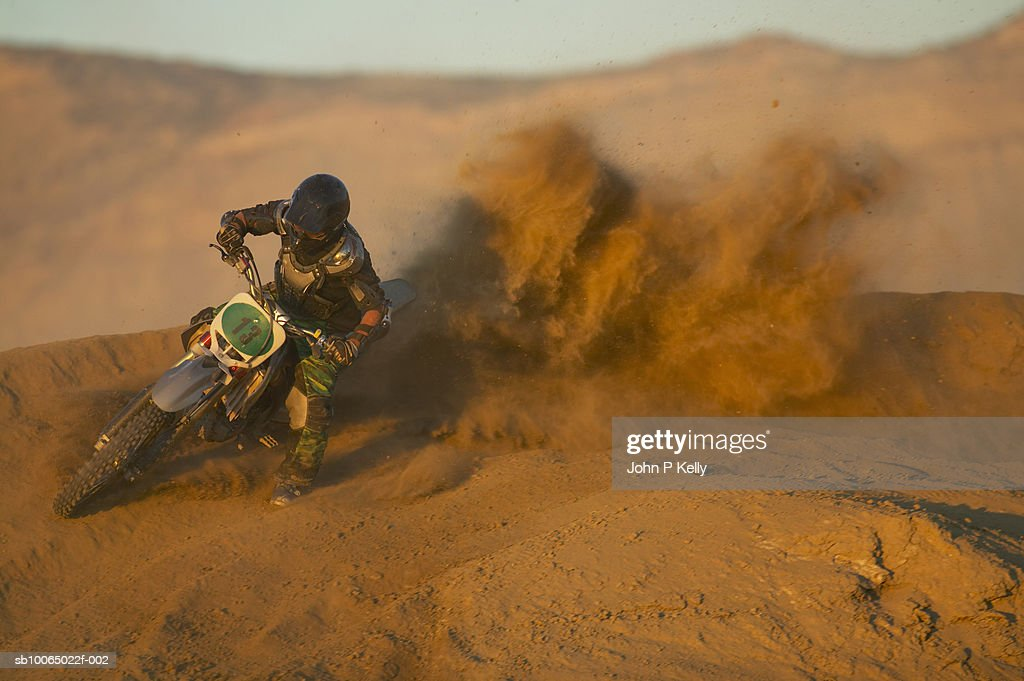 Man motocross riding in desert terrain, bike throwing up dirt : Stock Photo