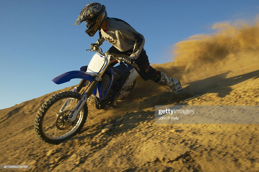 Man motocross riding in desert terrain : Stock Photo