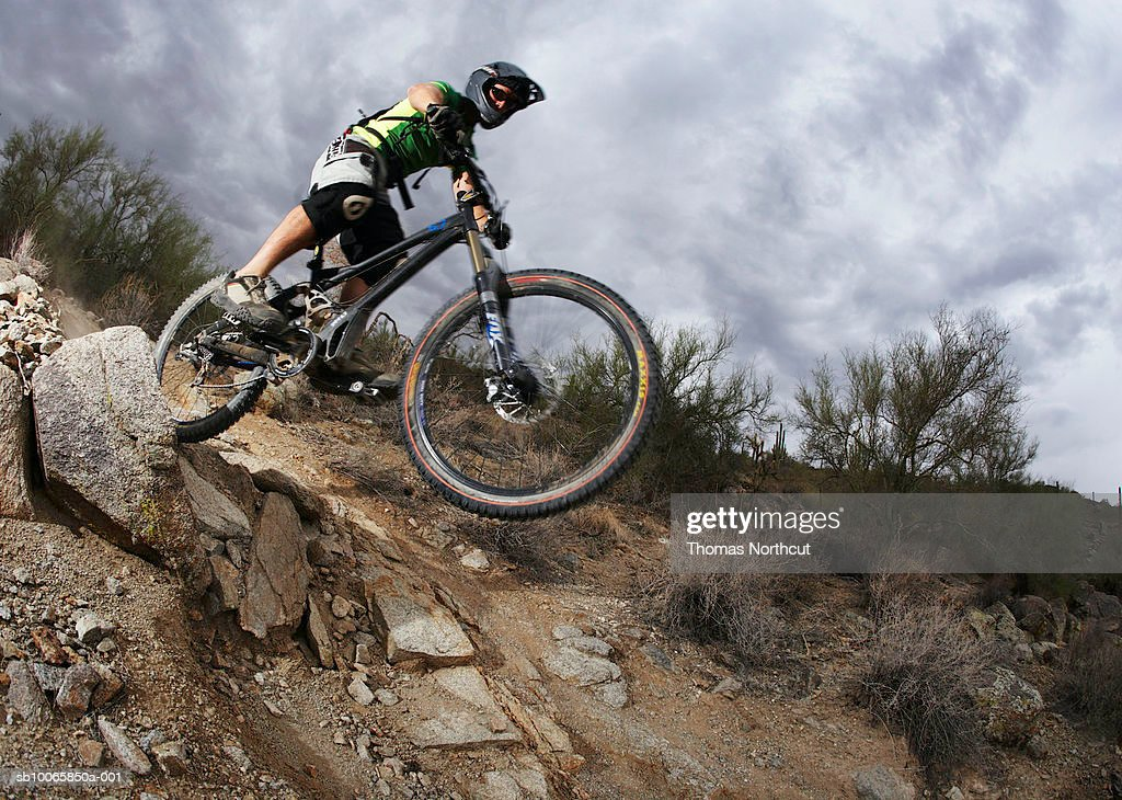 Man mountain biking down steep rocky path, low angle view : Stock Photo