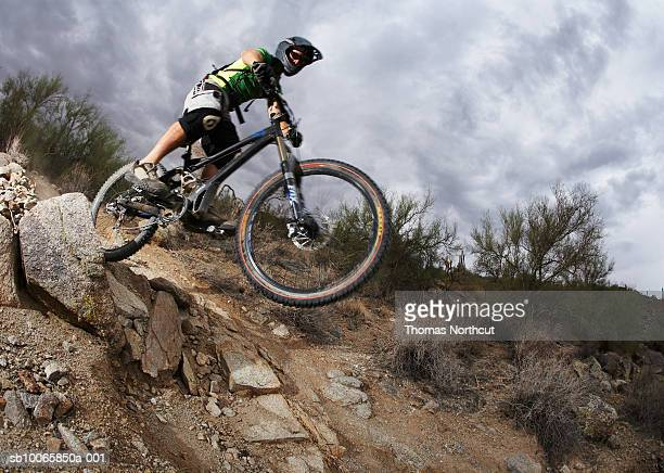 Man mountain biking down steep rocky path, low angle view