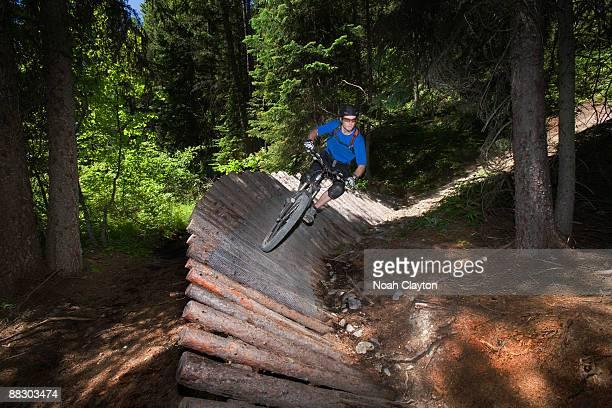 Man mountain biking on platform through woods