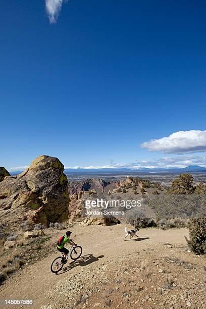 A man mountain biking with his dog.
