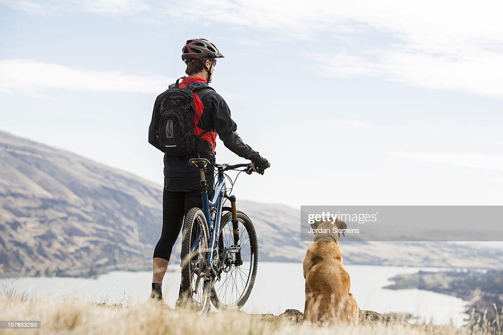 A man mountian biking with his dog.