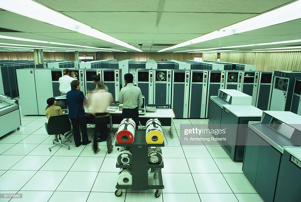 Man mounting magnetic tape on tape transport, supervisory console in front, high speed line printers on side. (Photo by H. Armstrong Roberts/Retrofile/Getty Images) : Stock Photo