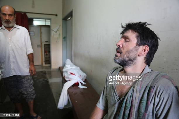 A man mourns over the dead bodies of his relatives at Sahra Hospital after Assad Regime's forces carried out their strikes over the deconflict zone...