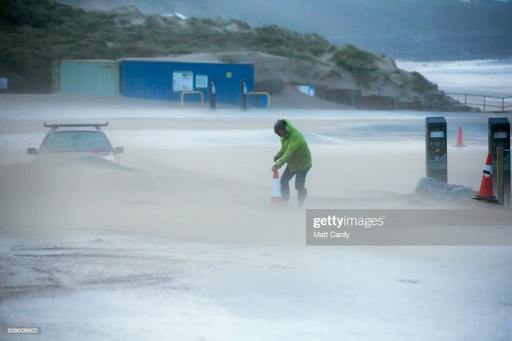 A man moves a traffic cone to close Fistral Beach car park because of strong winds on February 8, 2016 in Newquay, England. Parts of the UK are currently being battered by Storm Imogen, the ninth named storm to hit the UK this season. Thousands of homes have been left without power and commuters hit by road and rail chaos as Storm Imogen batters the South with gale force winds and torrential rain.