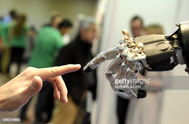A man moves his finger toward SVH automated hand made by Schunk during the 2014 IEEERAS International Conference on Humanoid Robots in Madrid on...