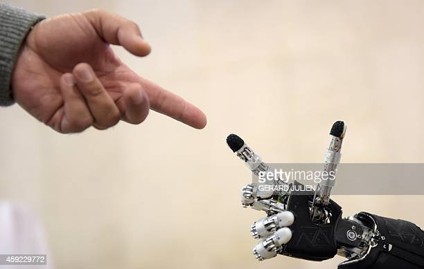 A man moves his finger toward the finger of humanoid robot iCub during the 2014 IEEERAS International Conference on Humanoid Robots in Madrid on...
