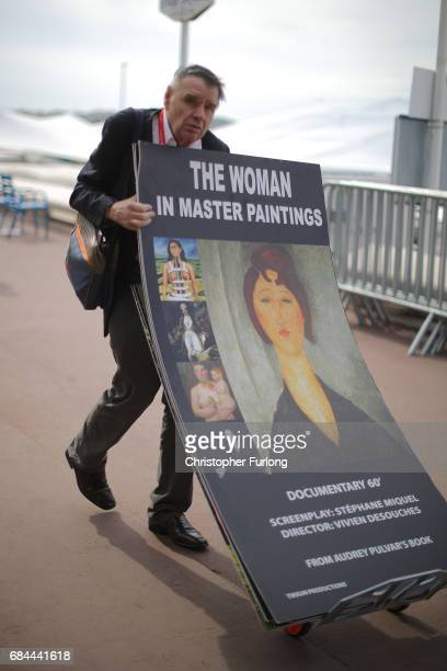 A man moves movie posters along the Boulevard de la Croisette during the Cannes Film Festival on May 18 2017 in Cannes France Celebrities fans and...