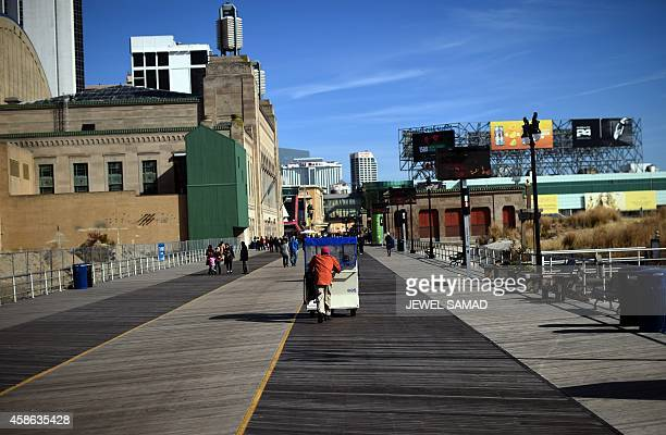 A man moves passengers on a 'push cab' along the boardwalk in Atlantic City New Jersey on November 8 2014 For decades Atlantic City was a popular...