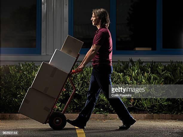 man moving boxes at night