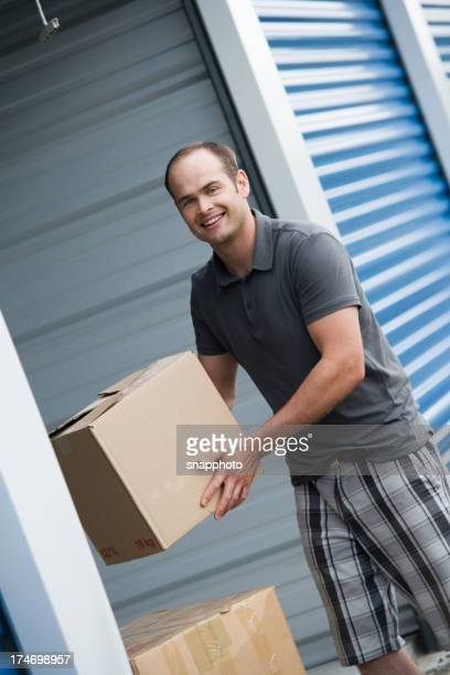 Man Moving Boxes Outside Self Storage Unit