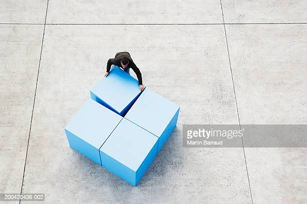 Man moving large blue blocks, elevated view