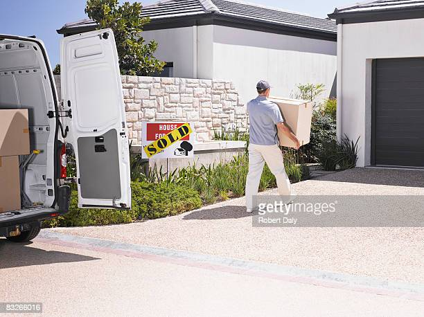 Man moving large box into new home