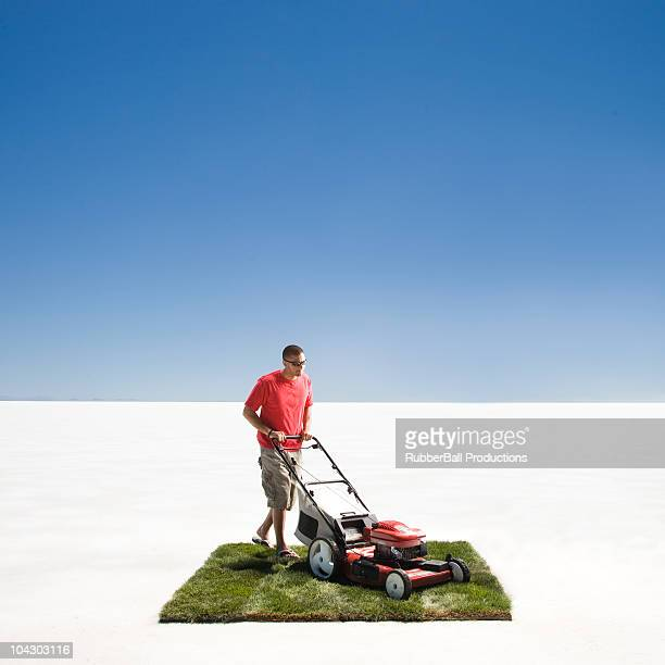 man mowing a small patch of grass in the middle of the desert