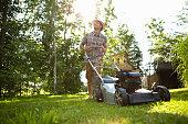Man mowing backyard lawn