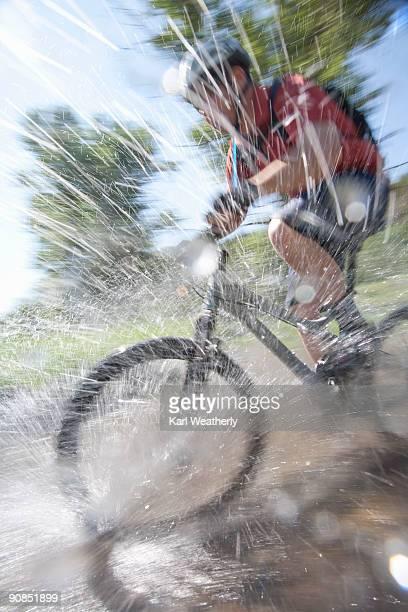 Man mt biking across stream