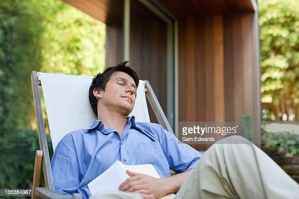 Homme, faire la sieste sur le patio tenant livre
