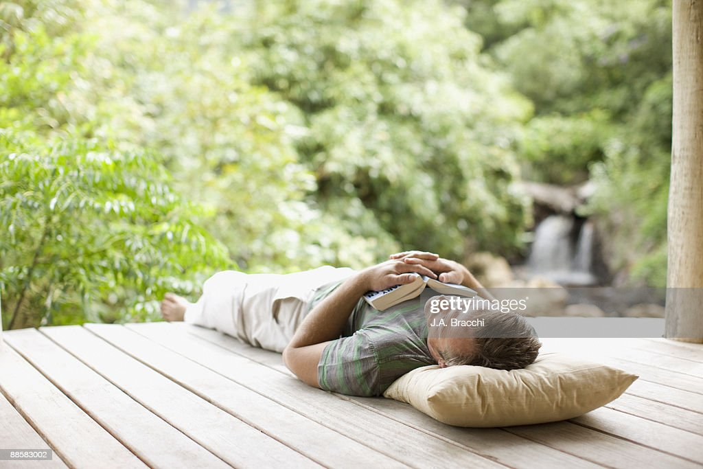 Man napping on porch in remote area : Stock Photo