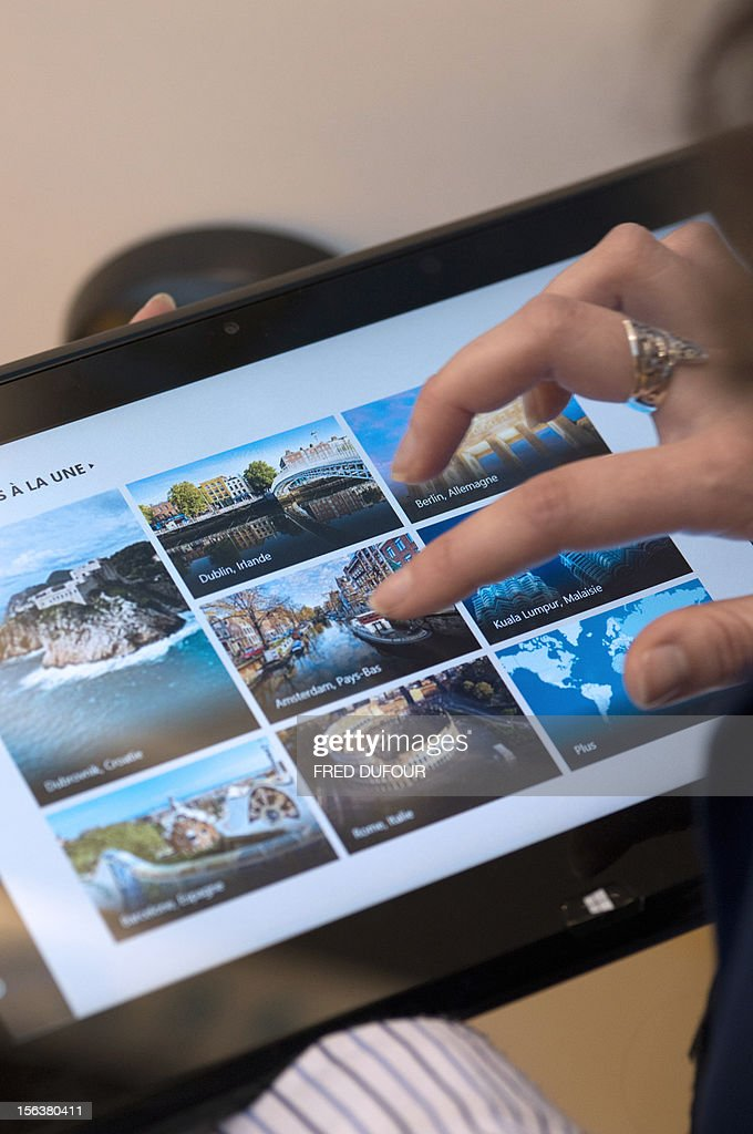 A man navigates with Windows 8 on a Tablet on November 14 2012 in Paris AFP PHOTO / FRED DUFOUR