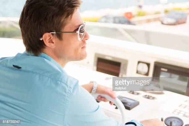man navigating his yacht