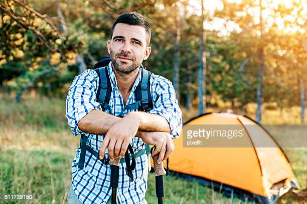 Man near a tent in the forest