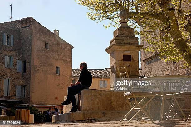 Mann in der Nähe von Brunnen in Gordes, Frankreich