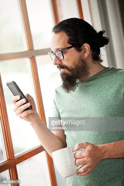 Man Near Large Window Checking Phone
