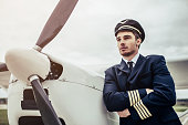 Young handsome man pilot in uniform is standing near small private plane.