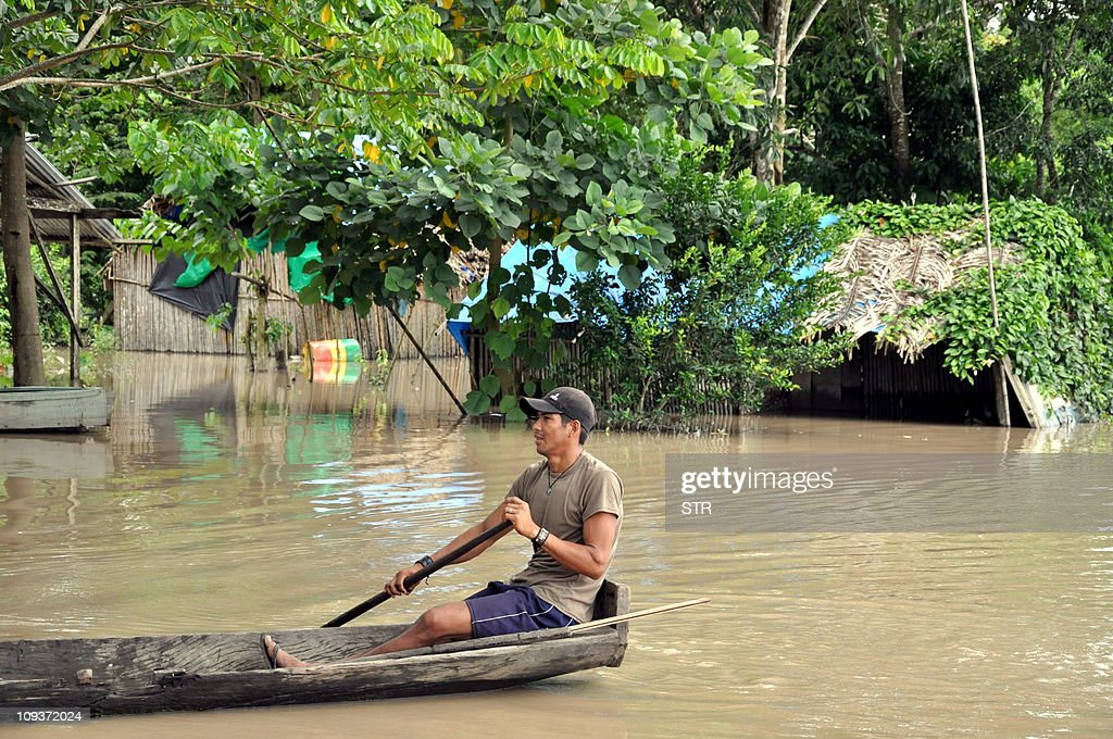 A man negociates a street on a pirogue in a flooded area of Puerto San Francisco, Chapare, Bolivia, on February 23, 2011. Five out of nine departments in Bolivia have been affected by heavy rains that have overflooded rivers, causing the death of four people, three more missing and forcing 6,900 inhabitants to abandon their home so far.