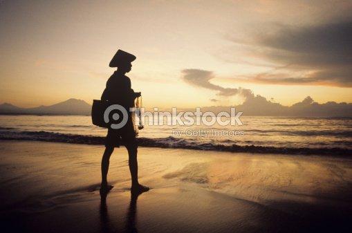 man net fishing on beach at dusk ストックフォト thinkstock