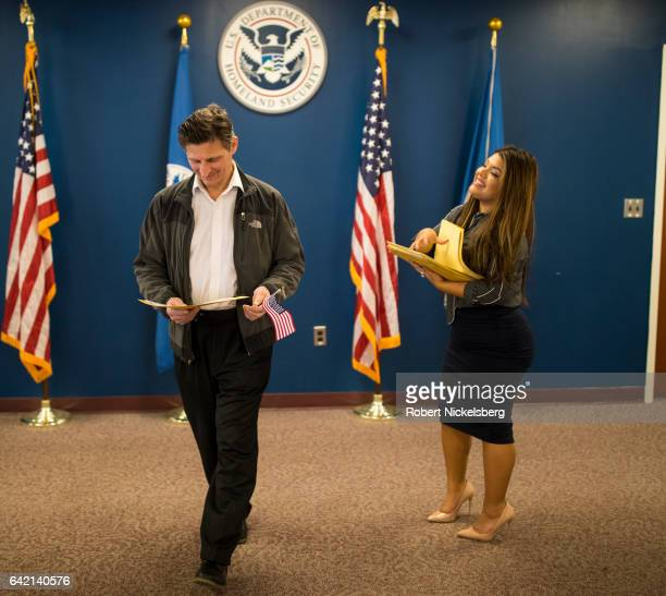 A man newly sworn in as a US citizen left receives his Certificate of Naturalization from a US government employee right during a naturalization...