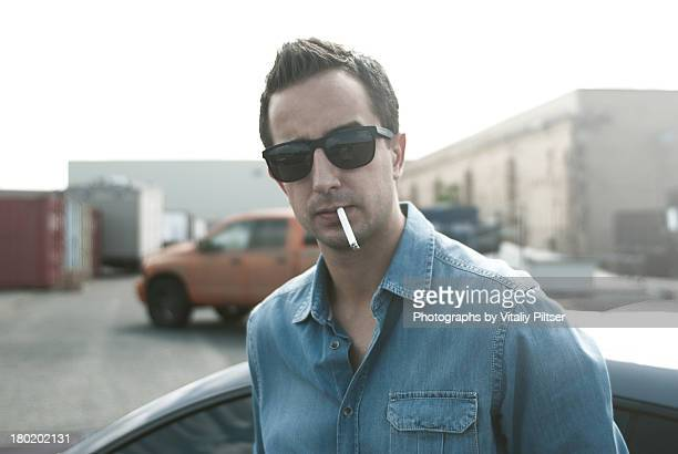 Man next to car with cigarette and sunglasses on.