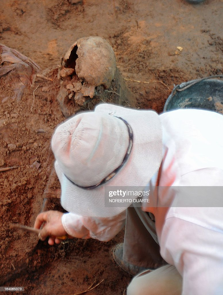 A man observes a human skull in the dirt on the premises of the Specialized Police Group headquarters in the outskirts of Asuncion on March 19, 2013. The human remains are believed to have been buried in the 1970´s, during the dictatorship of Alfredo Stroessner (1954-1989), in which hundreds went missing. AFP PHOTO/Norberto Duarte