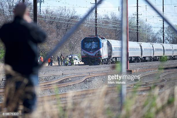 A man observes the crash site of Amtrak Palmetto train 89 on April 3 2016 in Chester Pennsylvania Two people are confirmed dead after the lead engine...