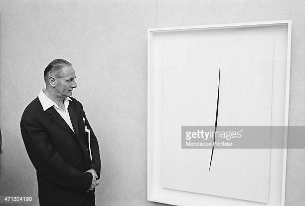 A man observing a Concetto Spaziale by Lucio Fontana displayed at the 32nd Art Biennale Venice June 1964