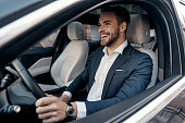 Handsome young man in full suit smiling while driving a car