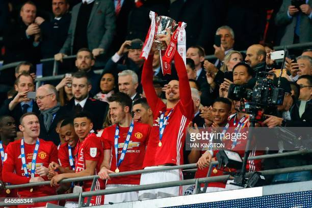 TOPSHOT Man of the match Manchester United's Swedish striker Zlatan Ibrahimovic lifts the trophy as Manchester United players celebrate their victory...