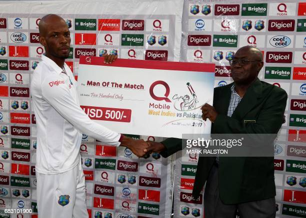Man of the Match Roston Chase of the West Indies receives his award from Dominica official Norbert Phillip after Pakistan won the final test match...